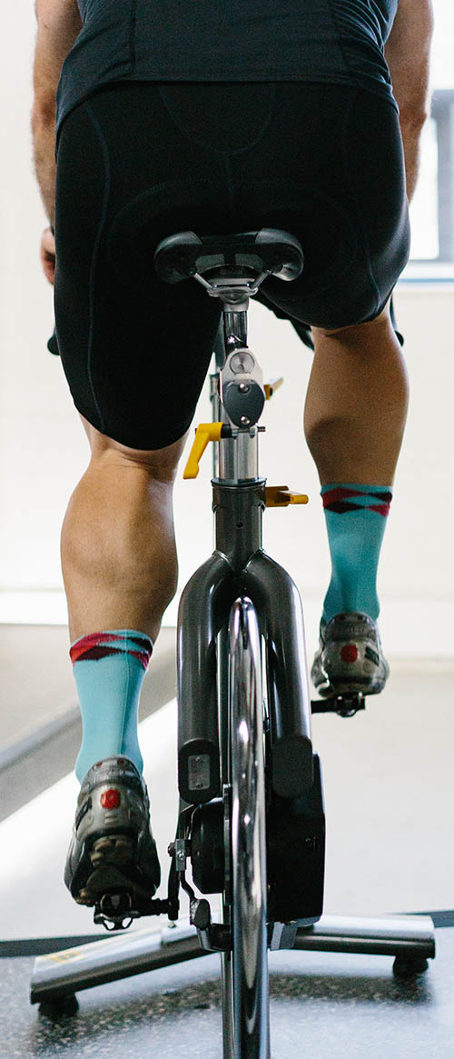 Rear view of indoor cyclist with great calves